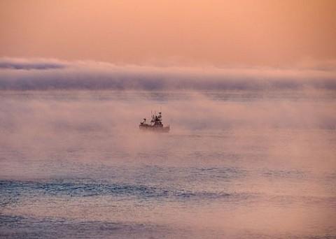 気嵐の中に出航する漁船