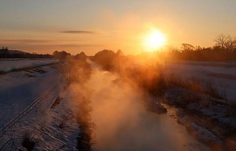 朝日に染まる川霧と熱気球